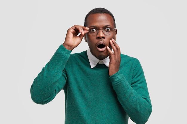Испуганный темнокожий парень с отвисшей челюстью от страха замечает ужасную сцену впереди, одет в зеленый джемпер, в очках
