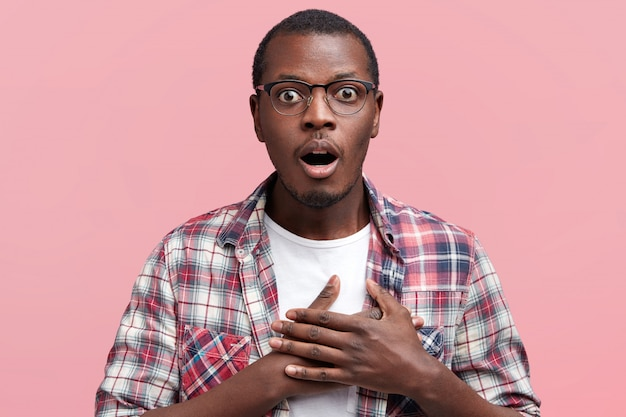 Scared dark skinned male looks with frightened expression, keeps hands on chest, being puzzled to notice something strange