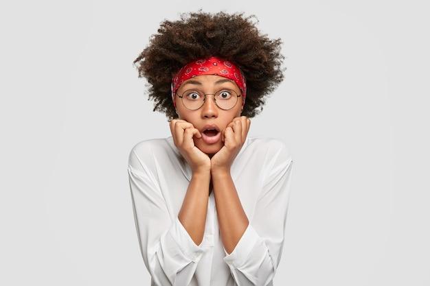 怖い暗い肌の女性は恐怖から口を開け、あごの下に手を保ち、白い特大のシャツと赤いヘッドバンドを着たひどいものを見て、巻き毛のふさふさした髪をしています。感情の概念。