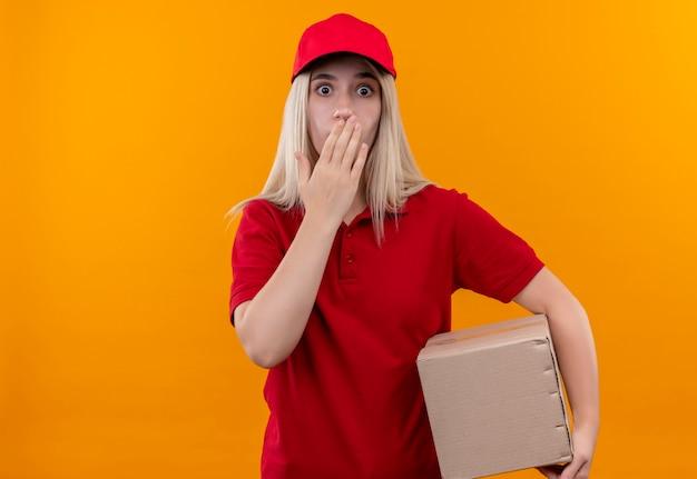 赤いtシャツとキャップ保持ボックスを身に着けている怖い配達少女は孤立したオレンジ色の背景に彼女の手を口に置きます