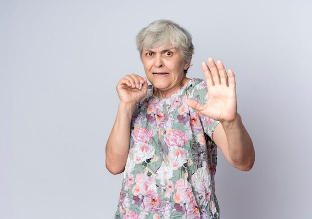 La donna anziana spaventata sta con le mani alzate isolate sulla parete bianca