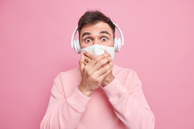 Испуганный эмоциональный взрослый мужчина прикрывает рот руками в защитной маске, опасаясь заражения коронавирусом, слушает музыку через стереонаушники, одетый в свитер