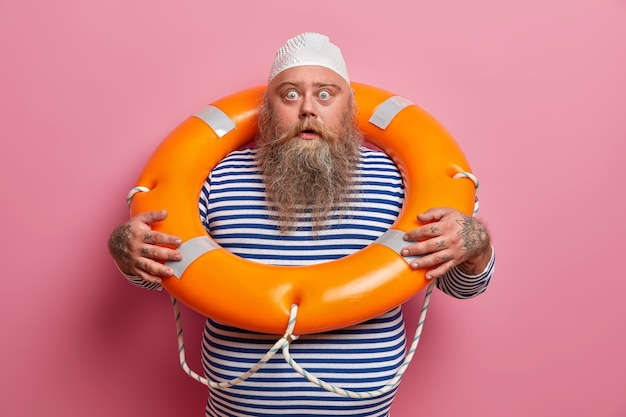 겁에 질린 감정적 인 수염 난 남자는 충격을받은 시선으로 쳐다보고, 라이프 링으로 포즈를 취하고, 줄무늬 선원 셔츠를 입고, 해변에서 물 휴양과 여름 휴가를 즐기고, 분홍색 벽에 고립