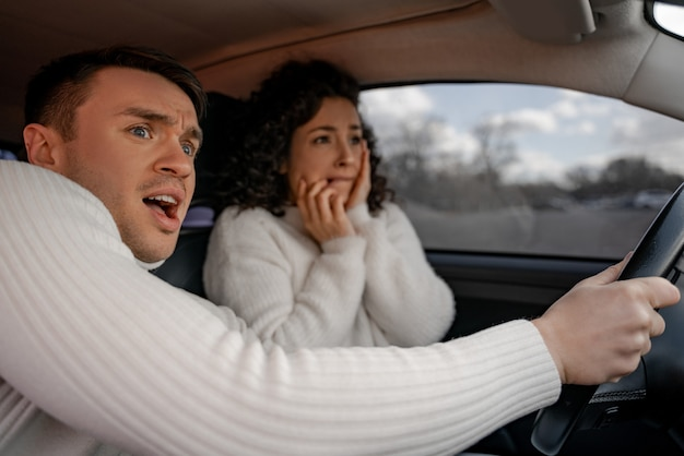 事故で個人の自動車で怖がっているヨーロッパのカップル。美しい巻き毛の女の子と大人の男はショックを受けています。男性は女性からハンドルを握ります。車の運転の概念