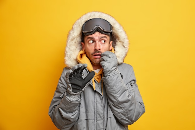 Испуганный европейский мужчина в верхней одежде с меховым капюшоном отдыхает в горах, занимается экстремальными видами спорта, активно отдыхает в холодное время года.