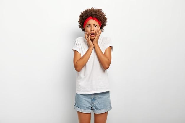La donna dai capelli ricci eccitata spaventata guarda nervosamente alla macchina fotografica, tocca le guance
