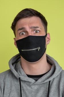 怖い目。黄色のスタジオの壁に分離された白人男性の肖像画。黒のフェイスマスクの気紛れな男性モデル。人間の感情、顔の表情、販売、広告の概念。異常な外観。