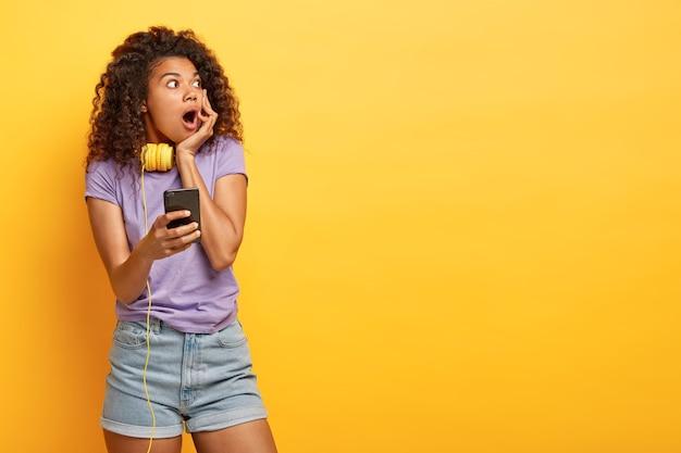 Spaventata spaventosa donna afro controllata calendario sullo smartphone, si dimentica del grande evento, distoglie lo sguardo con la bocca spalancata, vestita con abiti casual