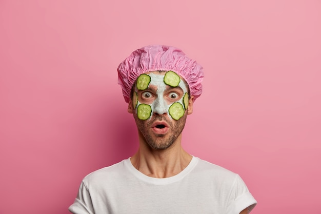 Uomo impaurito spaventato con espressione sorpresa, applica una maschera di argilla con fette di cetriolo verde, tiene la bocca aperta