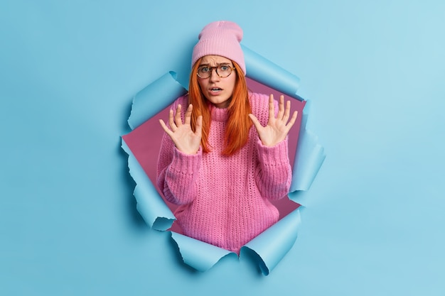 Scared fearful woman raises hands in defensive gesture sees something horrible wears pink hat and sweater breaks through paper expresses negative emotions.