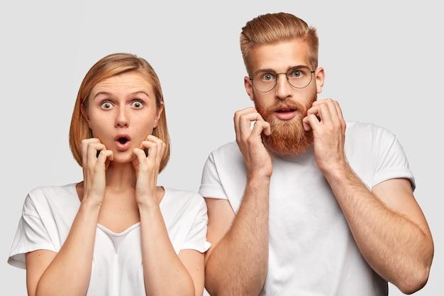 怖がっている女性と男性は、目がバグで見つめ、おびえているように見え、何か悪いことに気づいたり聞いたりし、カジュアルな白いtシャツを着て、頬に手をかざします。同僚は締め切りを逃すことを心配しています。