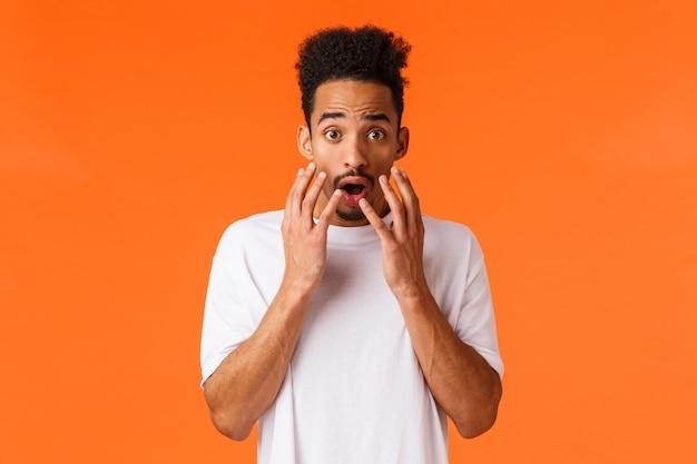 Испуганный, испуганный и шокированный афроамериканский молодой хипстерский парень, смотрящий на что-то страшное или пугающее, обеспокоенный апельсином, держится за руки возле раскрытого рта