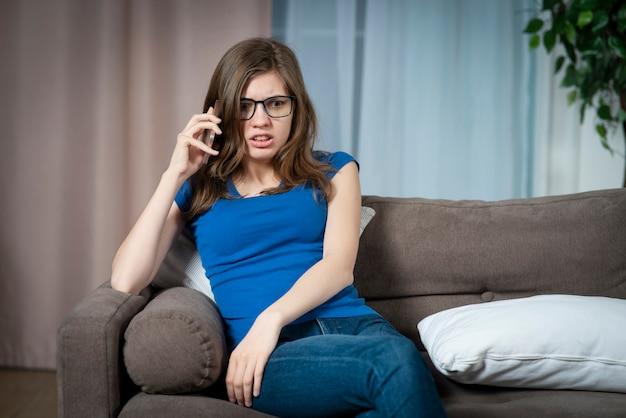 겁 먹은 소녀 안경을 쓴 화난 좌절한 여성이 휴대 전화 통화로 이야기하고 있습니다