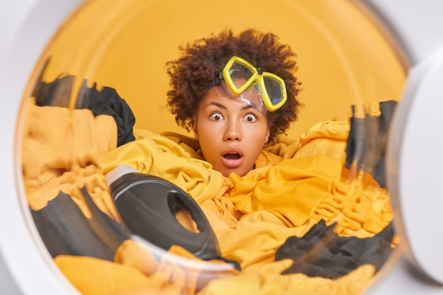 Scared frightened curly haired woman wears snorkeling mask on forehead drowned in laundry with bottle of detergent poses against yellow wall