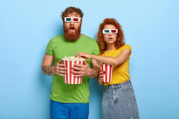 Coppia spaventata allo zenzero guarda film spaventoso, guarda con stupore, mangia popcorn, indossa occhiali stereo