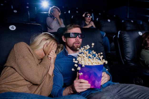 ホラーやアクション映画の間に3d眼鏡で男の肩に頭を保ちながら手で顔を覆う怖い女の子