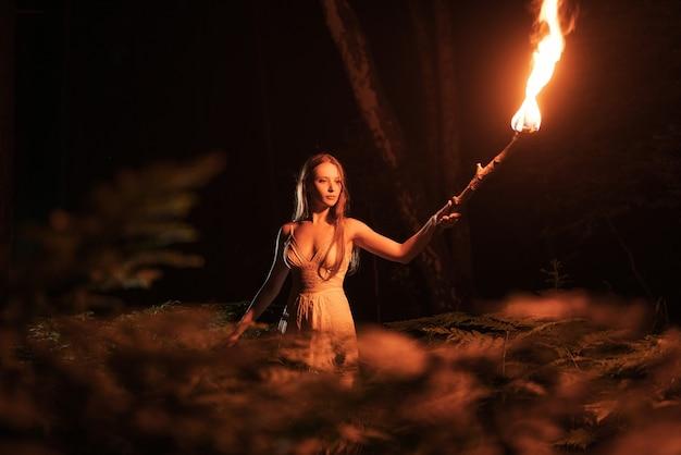トーチと暗い森の中で怖い女の子。