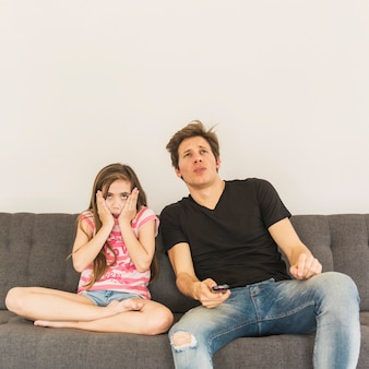 Scared girl sitting near her father on sofa