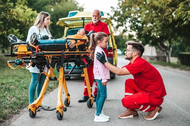 Испуганная девочка стояла рядом с раненой матерью и врачами. Premium Фотографии