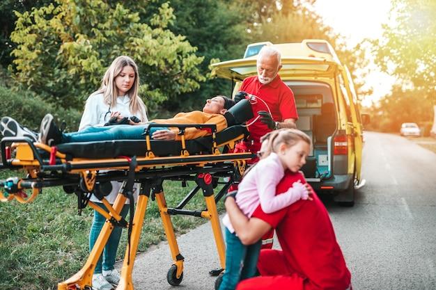 Испуганная девочка стояла рядом с раненой матерью и врачами.
