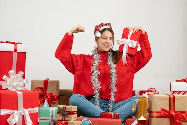 白のプレゼントの周りに座って勝利のジェスチャーを示すサンタの帽子を持つ怖い女の子
