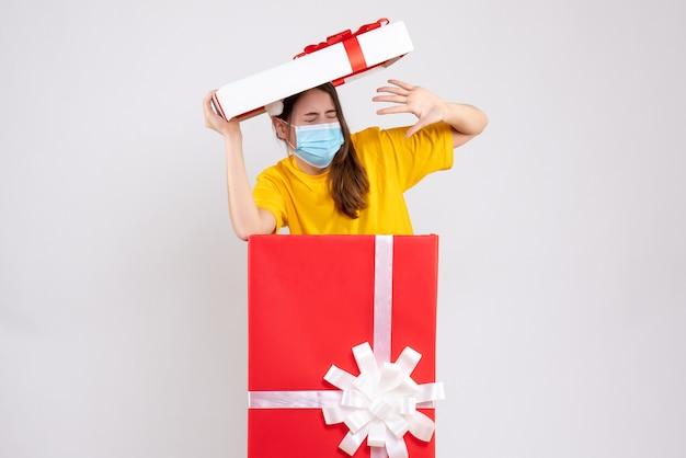 白の大きなクリスマスプレゼントの後ろに立っているサンタの帽子を持つ怖い女の子