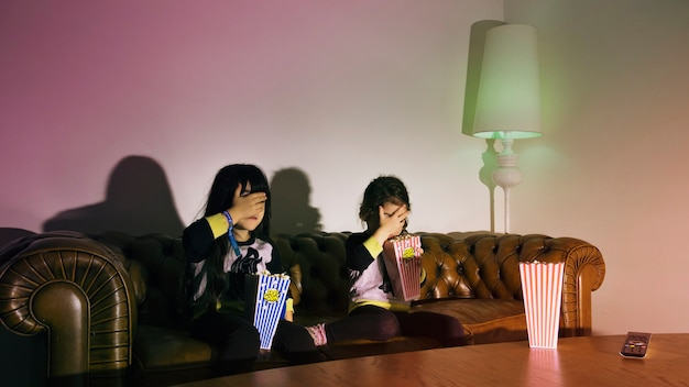 Scared girls with popcorn watching tv