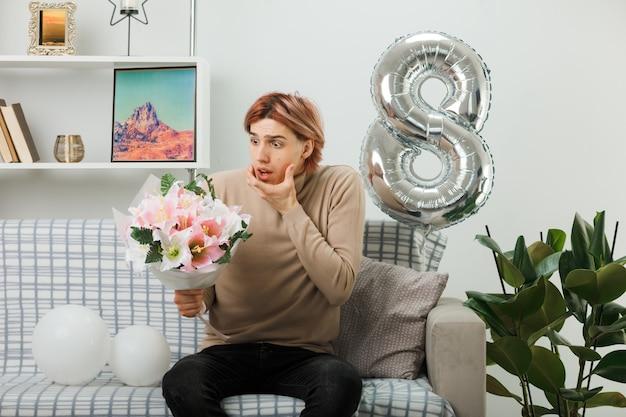 Un bel ragazzo spaventato ha afferrato il mento durante la giornata delle donne felici che tiene e guarda il bouquet seduto sul divano nel soggiorno