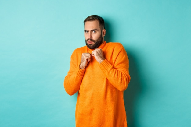 ターコイズブルーの壁を越えて、オレンジ色のセーターに立って、怖いものを見て、びっくりしてジャンプする怖い男。
