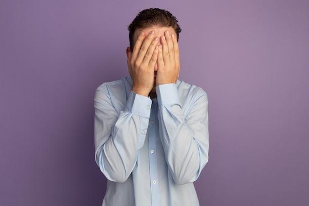 Uomo biondo bello spaventato mette le mani sul viso isolato sulla parete viola