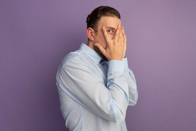 Uomo biondo bello spaventato si leva in piedi lateralmente mettendo le mani sul viso e guardando davanti attraverso le dita isolate sul muro viola