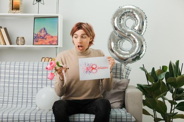 幸せな女性の日に怖いハンサムな男は、リビングルームのソファに座っているグリーティングカードで花を持って見ています