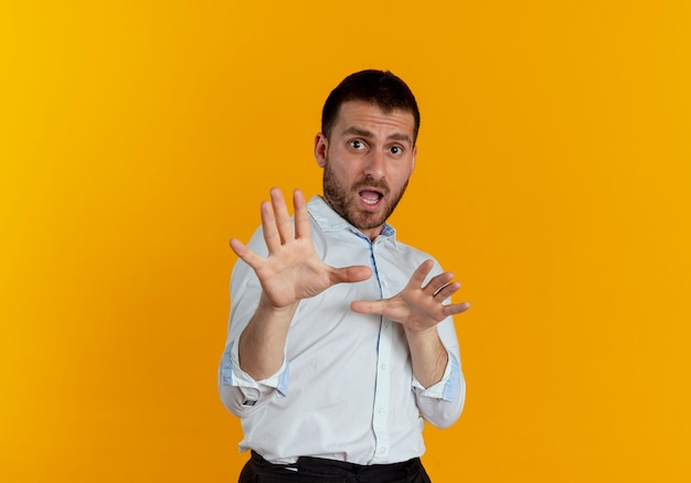 Scared handsome man pretends to defend with hands isolated on orange wall