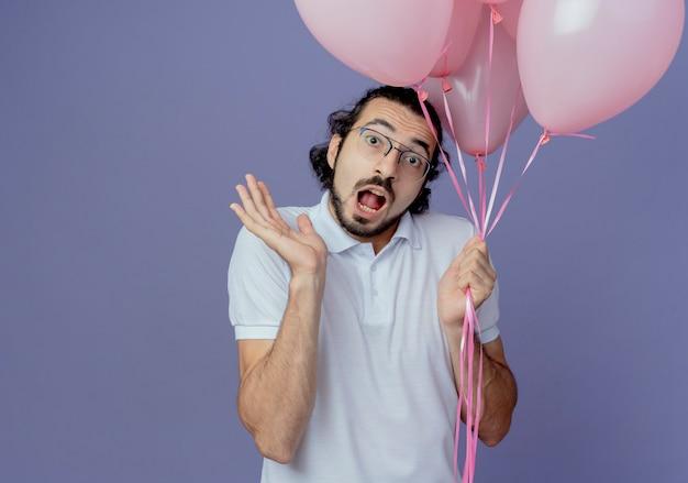 風船を保持し、紫に分離された手を広げて眼鏡をかけている怖いハンサムな男