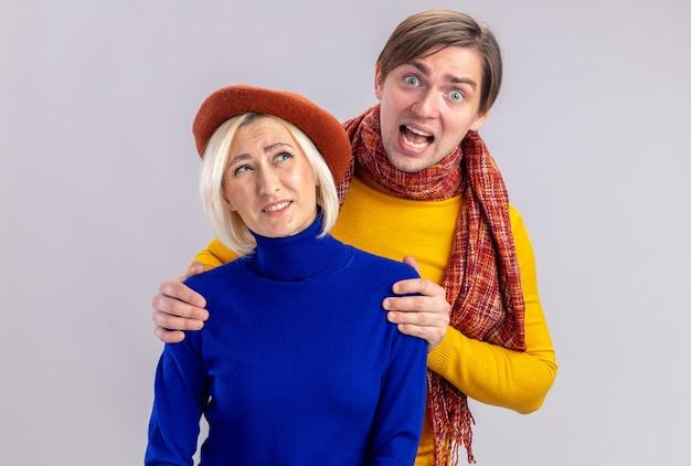 Un bell'uomo slavo spaventato con una sciarpa intorno al collo che tiene le spalle di una bella donna bionda scontenta con il berretto