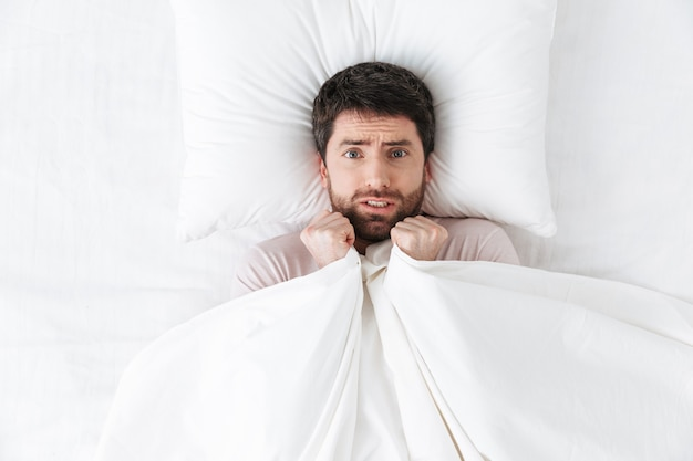 Scared handsome young man in the morning under blanket hide in bed