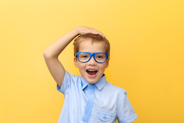 A scared, happy boy in a shirt and glasses clutched his head against a yellow wall