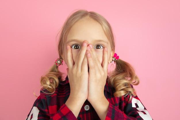 Испуганное сокрытие лица. портрет кавказской маленькой девочки на розовой стене.