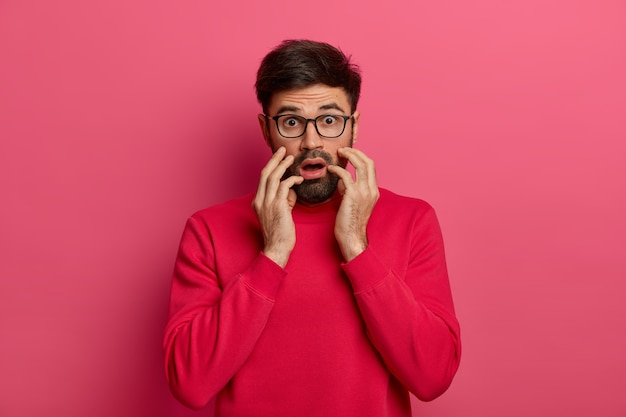 Scared horrified man stares , has phobia, feels afraid to death, has alarmed face expression, wears glasses, grabs face, isolated on pink wall. frightened male hears wild news