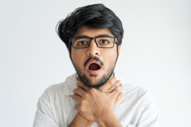 Scared indian man keeping mouth open and choking himself.