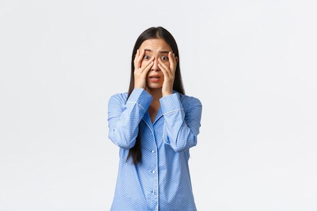 Испуганная неуверенная и робкая азиатская девушка в синей пижаме дрожит, глядя сквозь пальцы на что-то страшное, смотрит фильм ужасов во время ночевки, стоя на белом фоне.