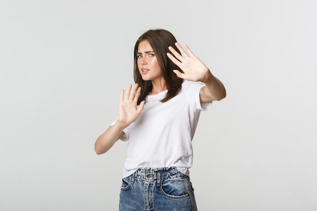 Scared and insecure cute girl raising hands in stop gesture, defending herself.
