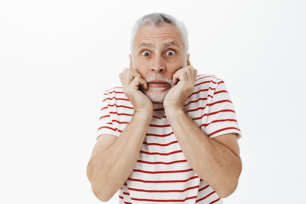 Scared and insecure elderly bearded man looking frightened and concerned