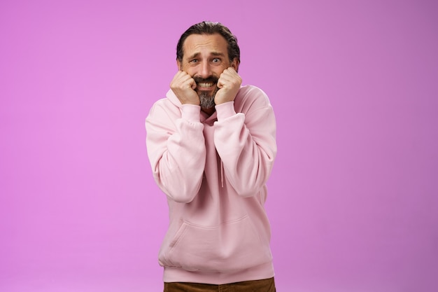 Scared insecure silly adult bearded man grey hair in pink hoodie press palms mouth bite fingers clench teeth shocked frightened widen eyes terrified standing stupor horrified, purple background.