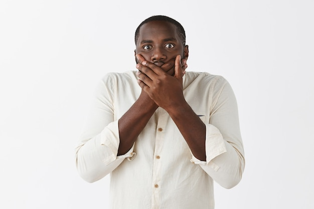 白い壁に向かってポーズをとる怖い不安な若い男