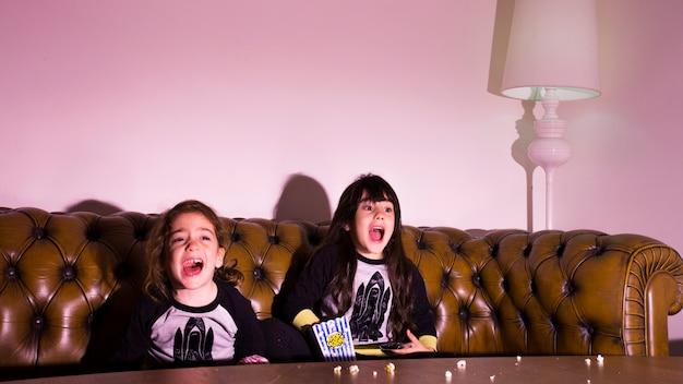 Испуганные дети смотрят фильм дома