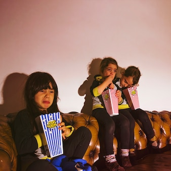 Scared kids with popcorn watching movie