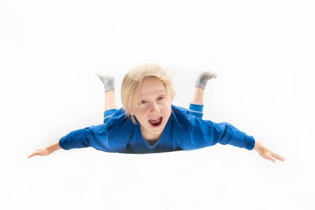 怖い金髪の少年が高さから落ちています。フリーフォール。白色の背景。