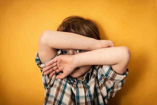 손으로 얼굴을 숨기는 겁 먹은 어린 소년. 가정 폭력과 학교 개념에서의 따돌림