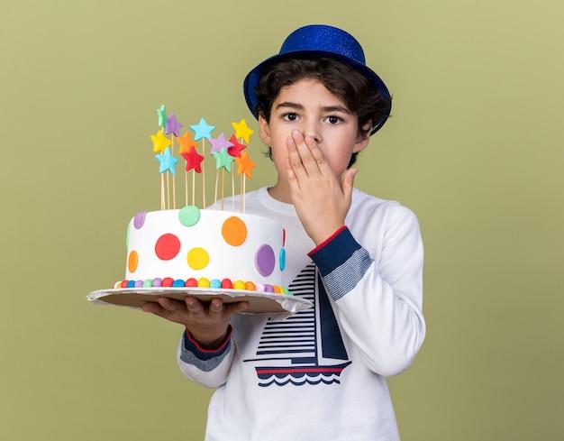 케이크를 들고 손으로 입을 덮고 파란색 파티 모자를 쓰고 겁 먹은 어린 소년